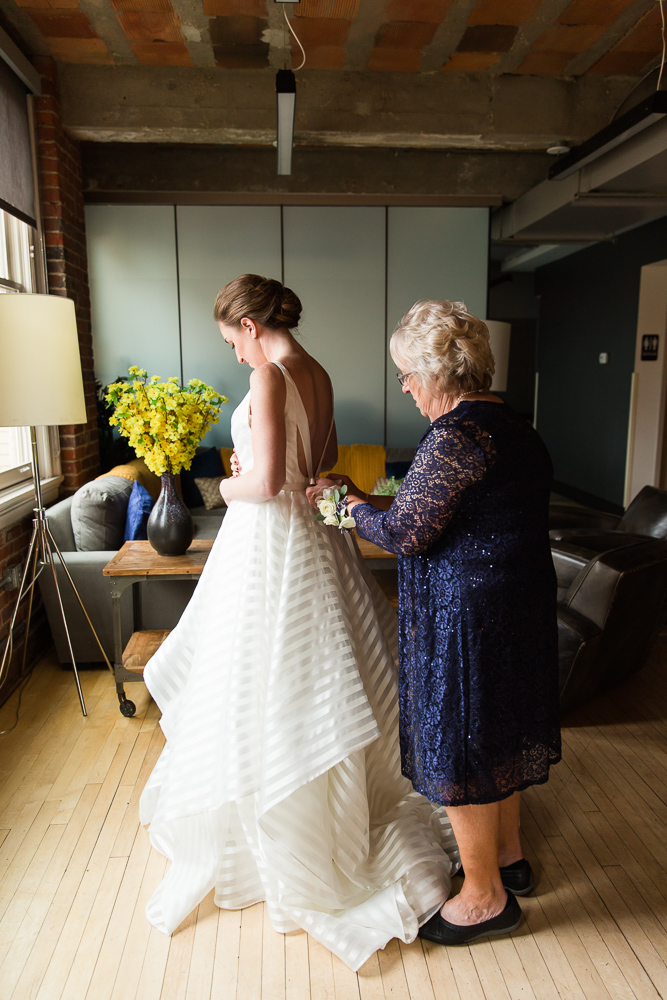 Bride's mother helping her put on her wedding dress at the Loft at 600 F | Washington DC Wedding