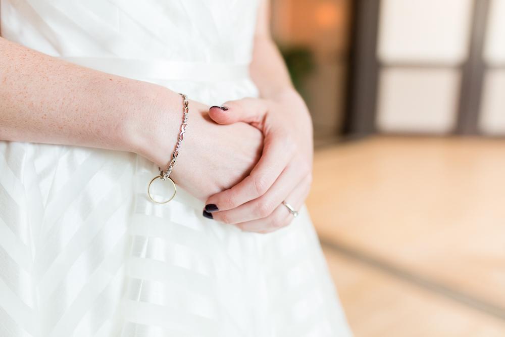 Bride's hands clasped over her wedding dress