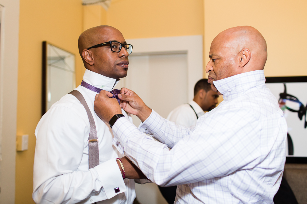 Father of the groom helping him put on his bow tie at the Kimpton Hotel Monaco