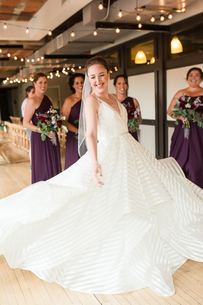 Smiling bride twirling in her Hayley Paige Decklyn wedding dress under the string lights at the Loft at 600 F wedding venue