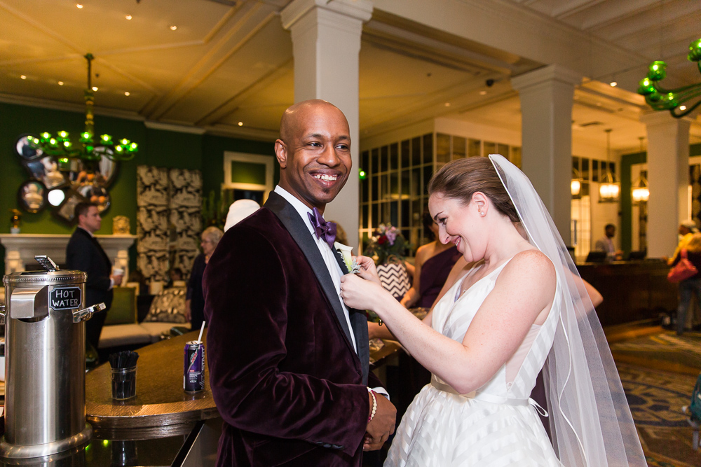 Bride pinning the boutonniere on the groom in the lobby of the Kimpton Hotel Monaco