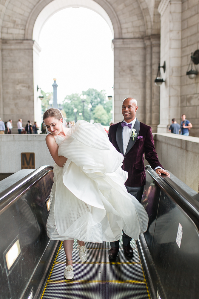 Bride holds her wedding dress while stepping off the escalator of the Metro at Union Station