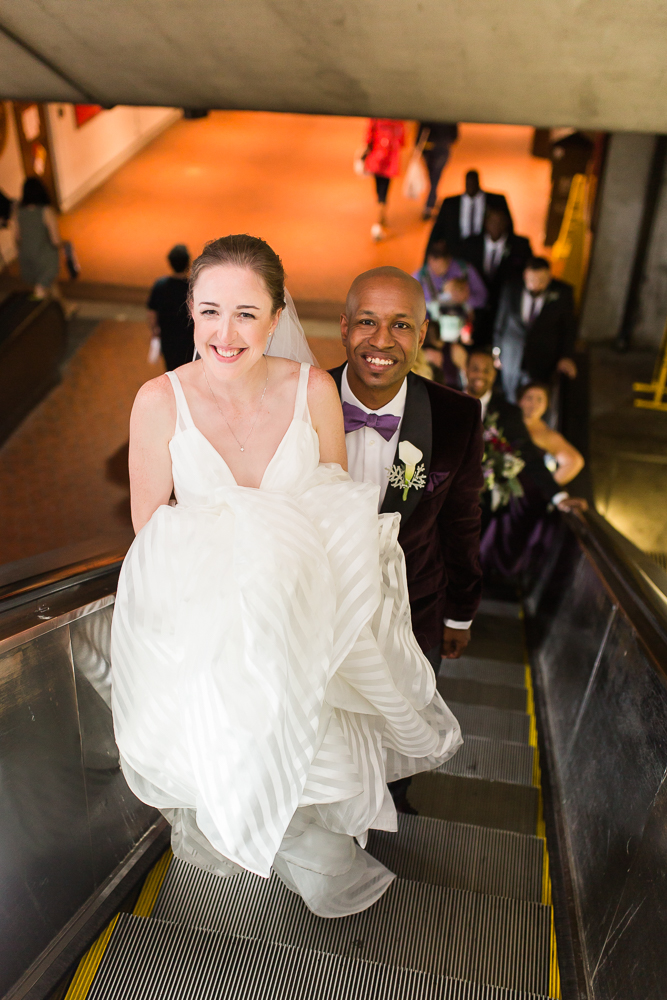 Wedding couple smiling up at the camera while riding the escalator at Union Station