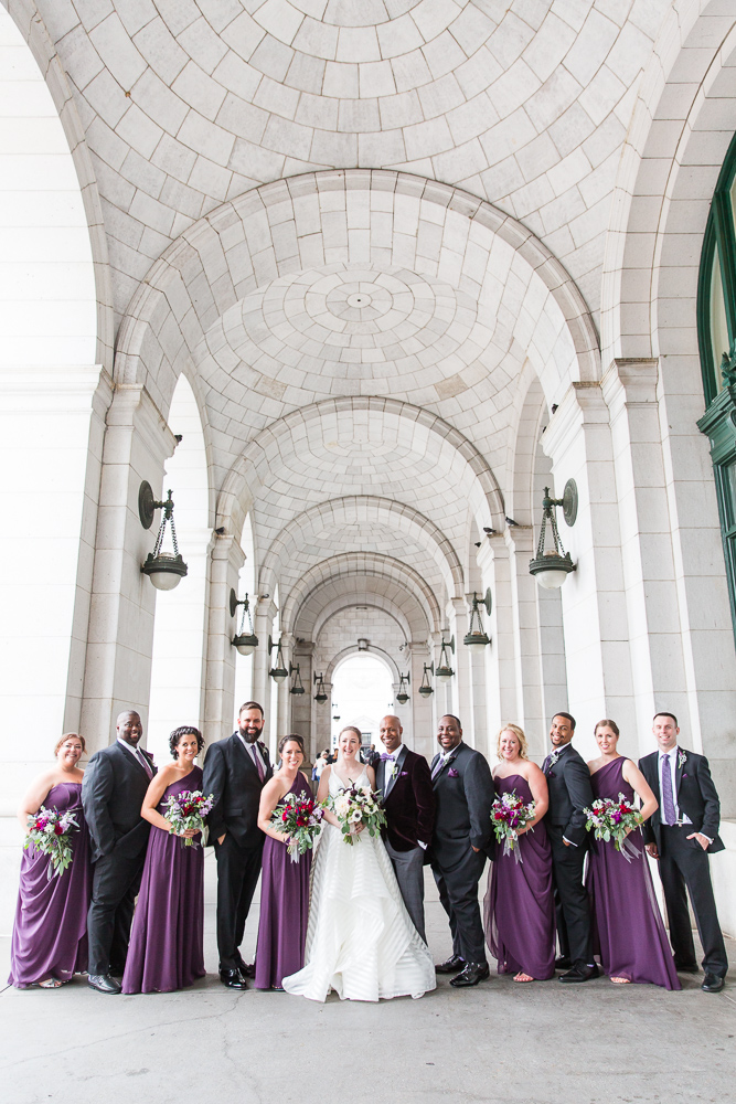 Wedding party in purple poses under the arches at Union Station