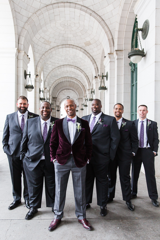 Groom standing with his groomsmen under the arches at Union Station | Best Washington DC wedding photo locations