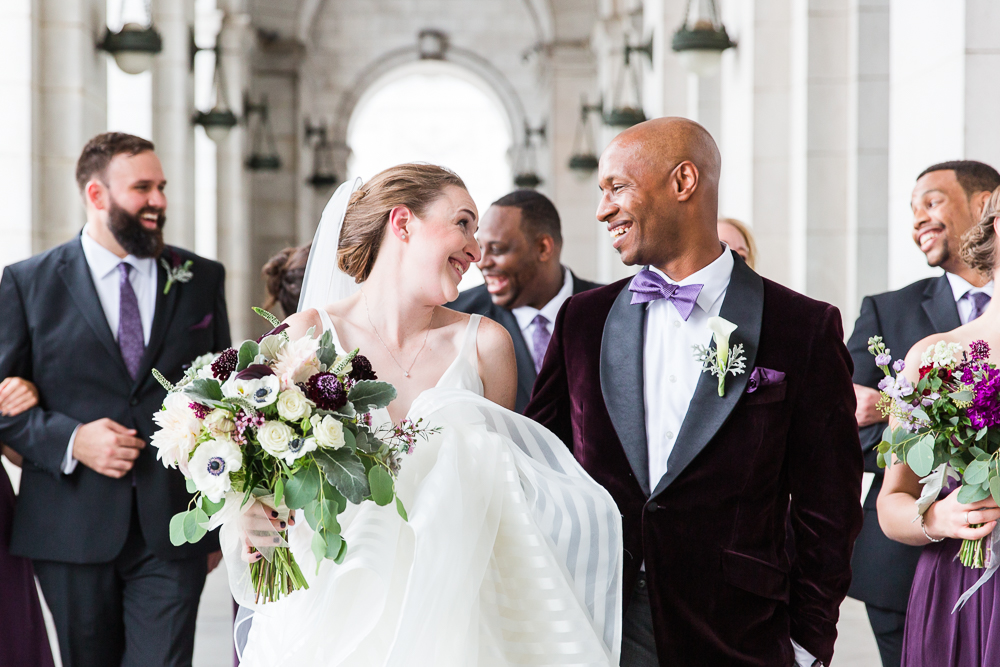 Bride and groom smiling at each other as they outside of Union Station with their bridal party