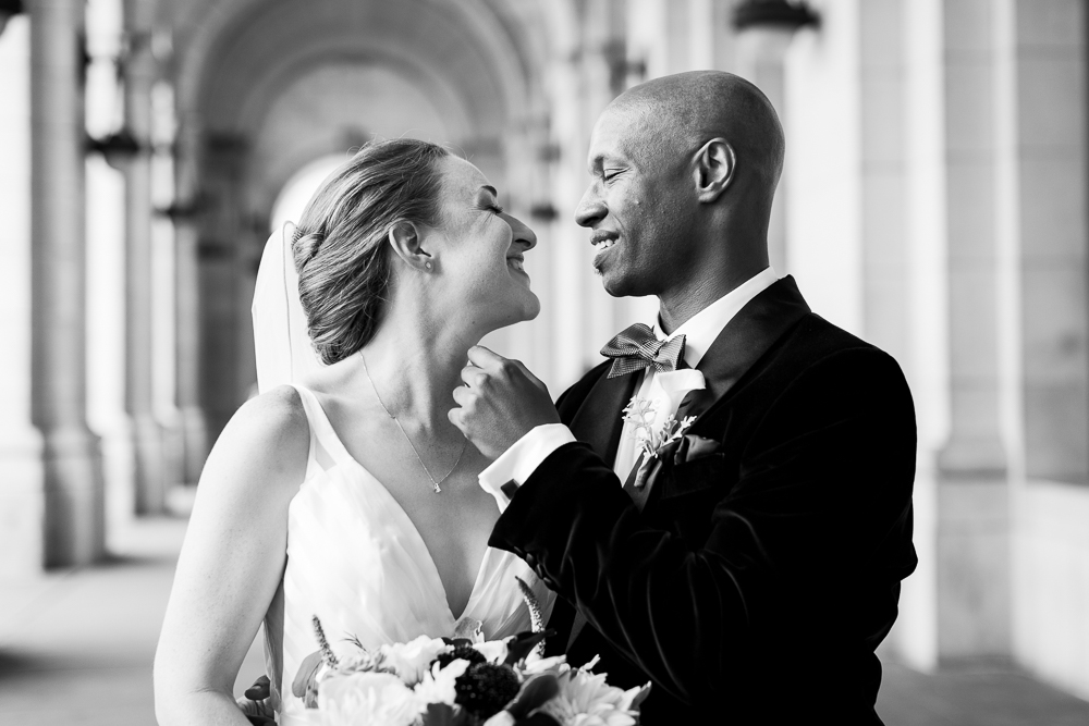 Black and white photo of bride and groom leaning in for a kiss