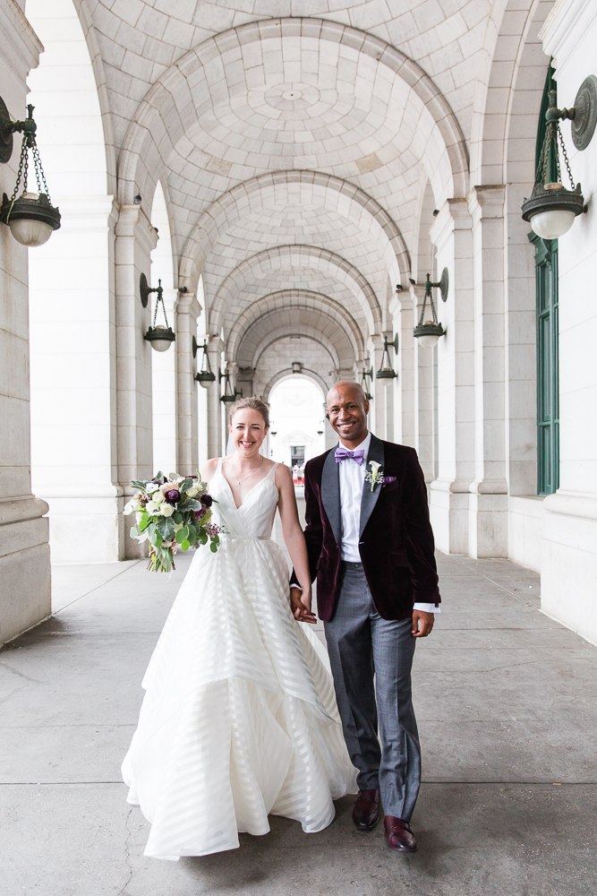 Husband and wife holding hands as they walk through Union Station in Washington, DC for their wedding pictures