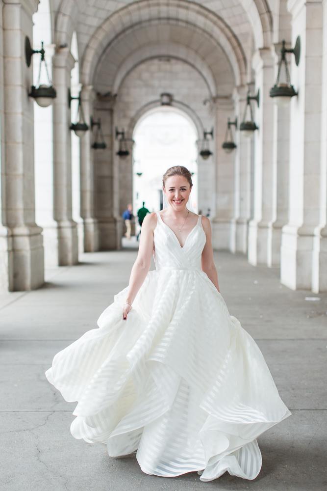Bride holding her wedding dress as she walks through the arches at Union Station | Washington, DC bridal portrait