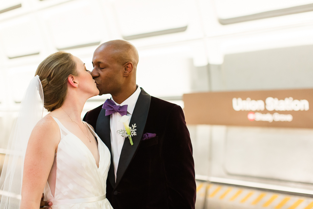 Bride and groom kiss while waiting for the Metro at Union Station in DC