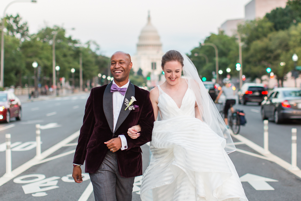 Bride and groom smiling as they walk along Pennsylvania Avenue with Capitol in the background | Best Washington DC Wedding Photography