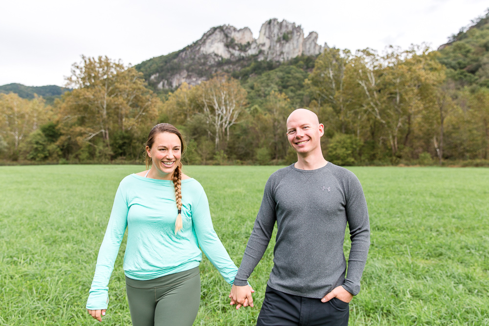 Engaged couple holding hands as the walk through the field in front of Seneca Rocks, West Virginia