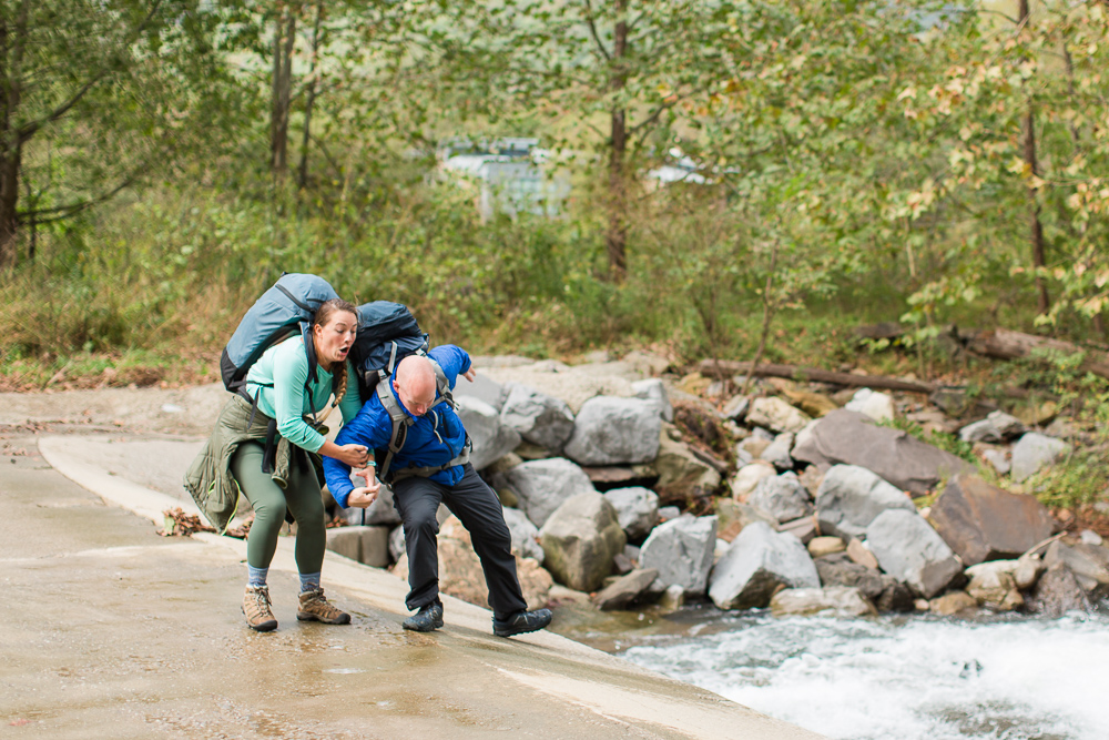 Candid moment of groom slipping and almost falling into the creek | Adventure engagement photography in Northern Virginia