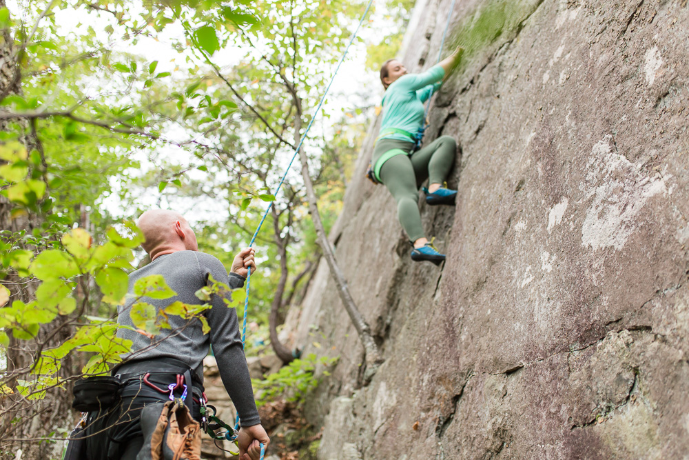 Watching his fiance rock climb during their engagement session at Seneca Rocks | Engagement photography for adventurous couples in Northern Virginia