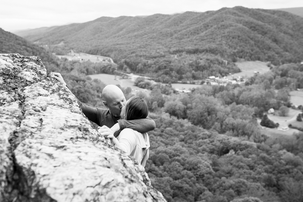 Black and white photo of engaged couple sharing a kiss as they reach the top of their Seneca Rocks climb | Documentary style engagement photography