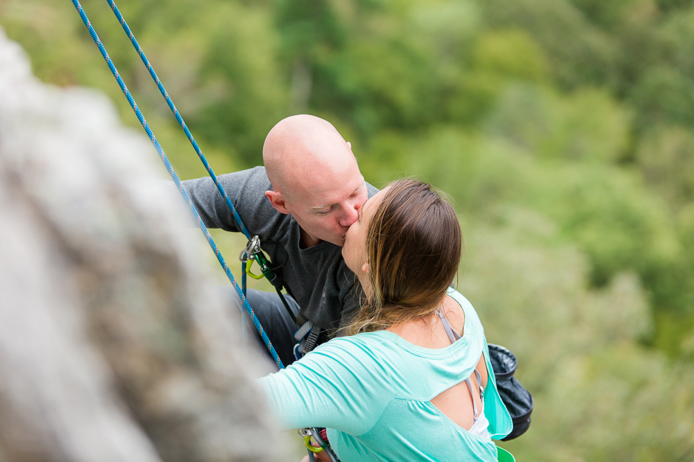 Happy couple kisses while harnesses in during a rock climbing engagement session at Seneca Rocks | Best Seneca Rocks photography