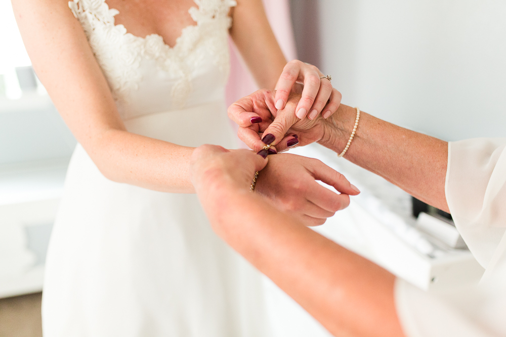 Mom helping bride put on her wedding day jewelry | Wedding detail photos