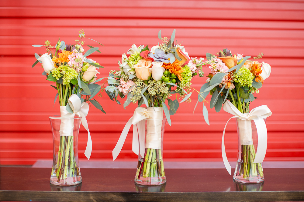 Wedding bouquets in vases in front of the red door at the Hangar at Stanley Marketplace
