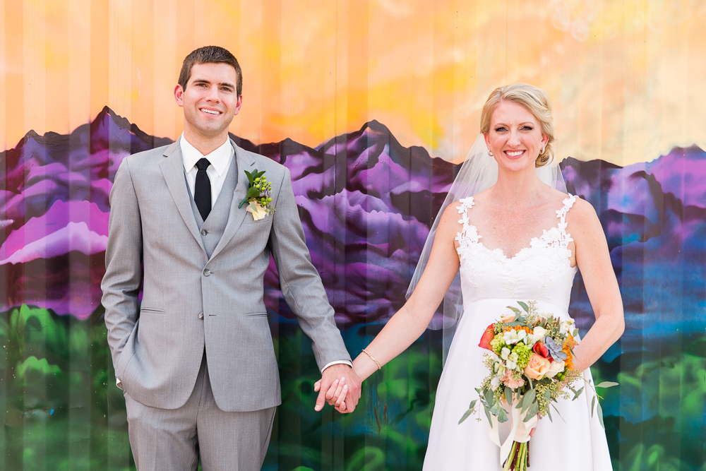 Wedding pictures in front of the mountain mural at The Hangar at Stanley Marketplace | Aurora, CO Wedding Photographer