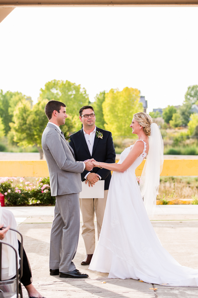 Bride and groom smiling during their outdoor wedding ceremony in Aurora, Colorado