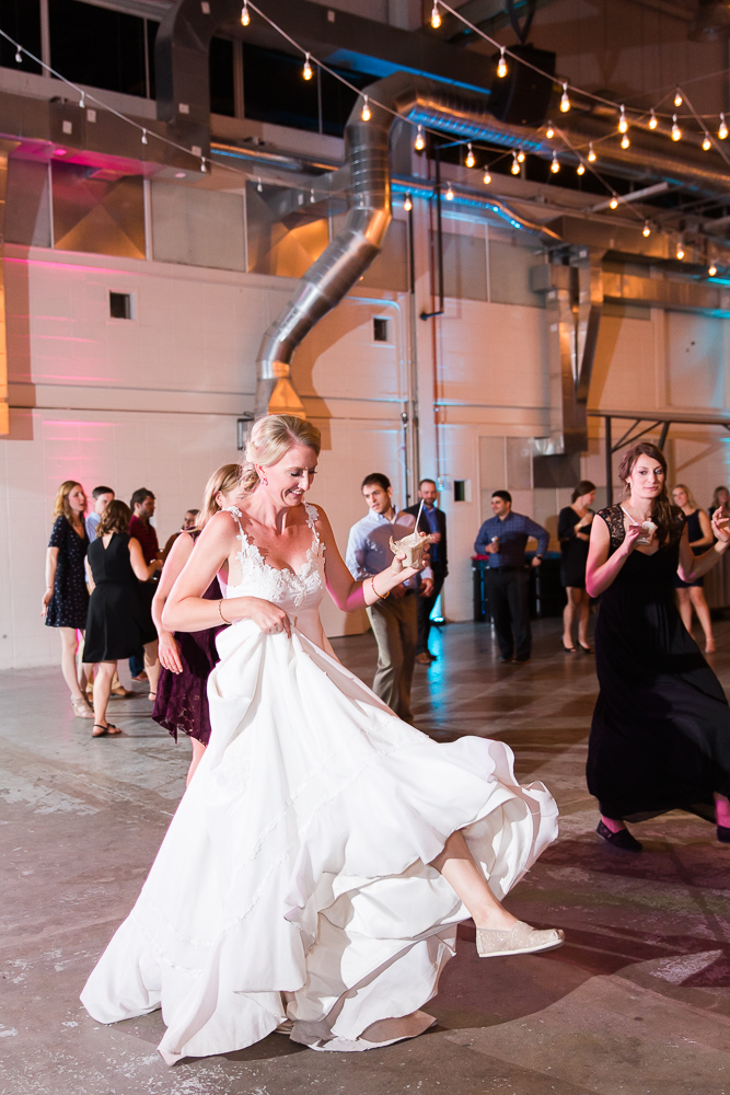Bride holding ice cream while dancing during her wedding reception at The Hangar at Stanley Marketplace in Aurora, CO