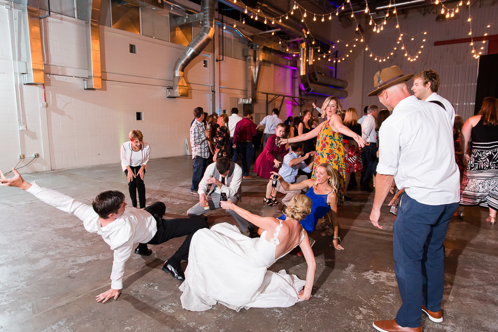 Bride and groom dancing with their wedding guests during reception at Hangar at Stanley Marketplace | Fun wedding pictures in Denver, CO