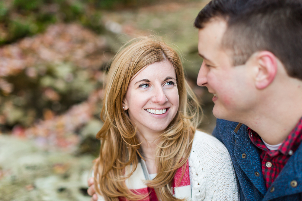 Looking into each other's eyes during their fall engagement session
