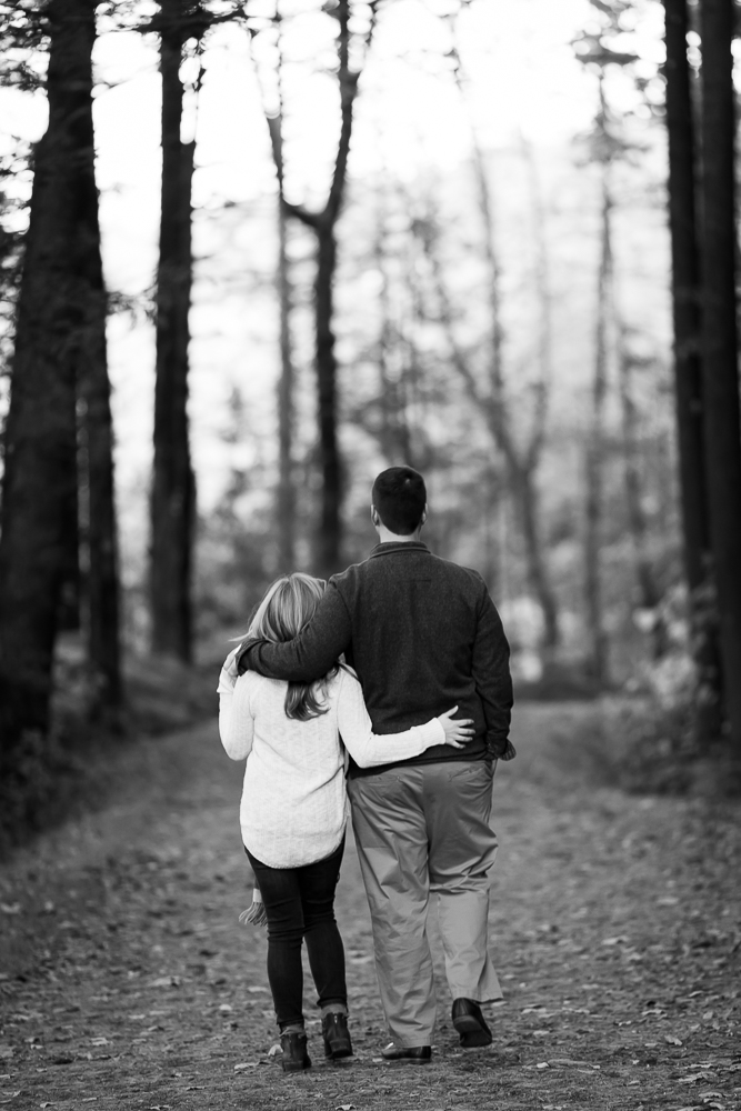 Black and white photo of couple with arms around each other as they walk down the trail | Hudson Valley engagement photographer