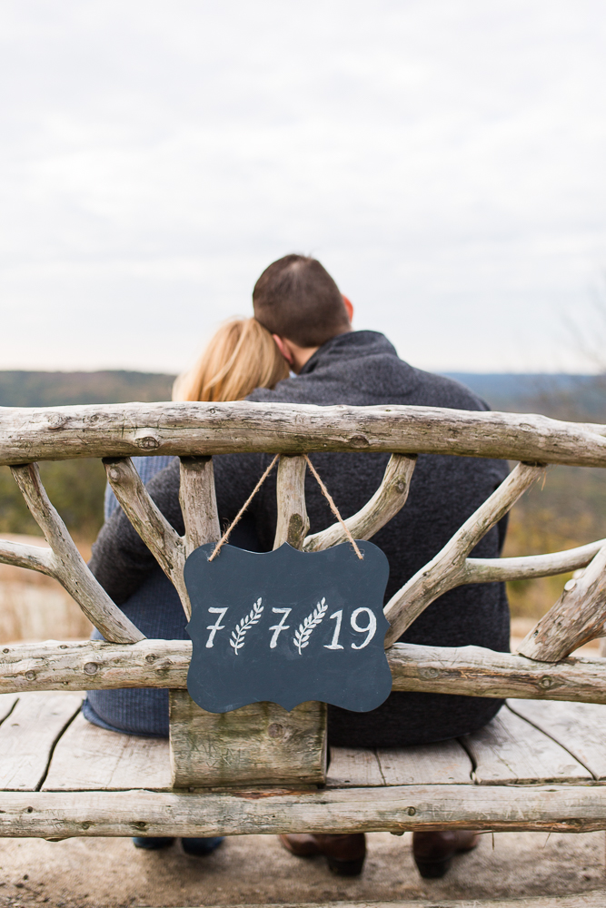 Wedding date sign hanging on the back of park bench during engagement shoot in the Hudson Valley