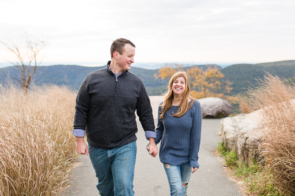 Smiling candid engagement photo, holding hands and walking through Bear Mountain State Park | Candid Hudson Valley Engagement Photography