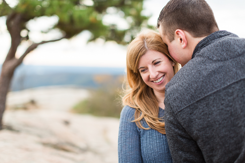 Engaged couple cuddling while overlooking the Hudson River at the top of Bear Mountain
