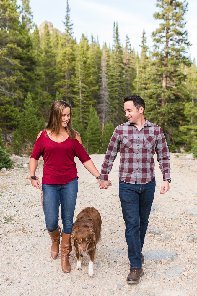 Couple holding hands while walking their dog on the rocky trail at St. Mary's Glacier | Colorado Engagement Photography