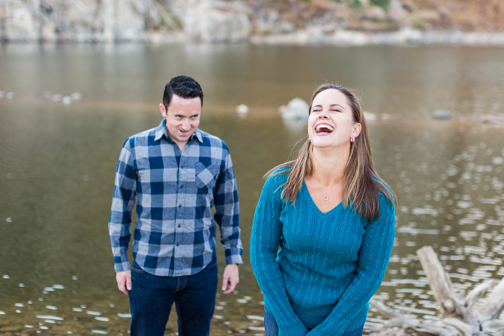 Happy couple goofing off by the lake at St. Mary's Glacier | Candid Engagement Photographer in Colorado
