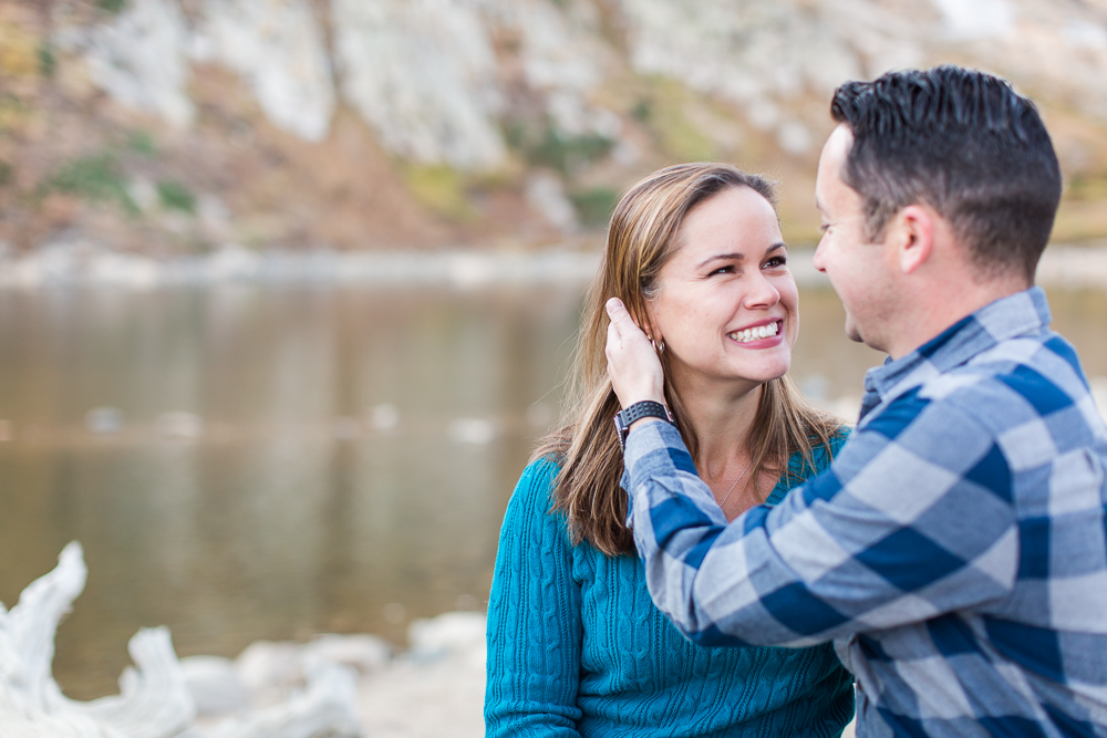 Smiling and looking into each other's eyes while taking pictures at St. Mary's Glacier | Best Colorado adventure engagement photo spots