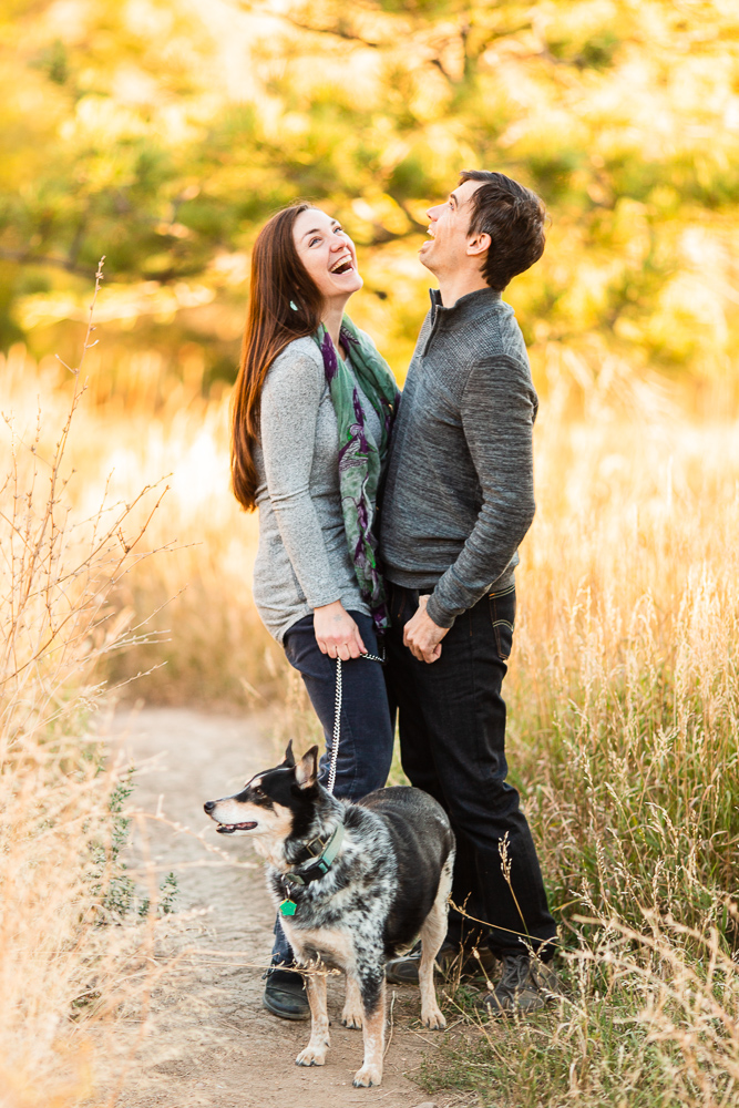 Candid photo of couple on the trail with their dog at Chautauqua Park during golden hour | Boulder Colorado Engagement Photographer