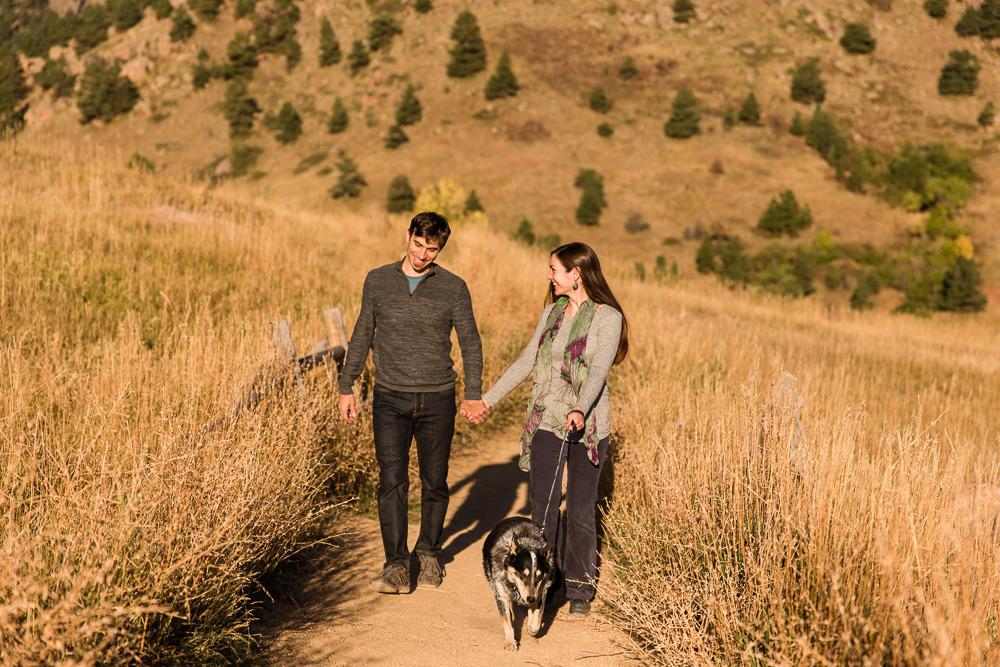 Couple holding hands as they hike the trails at Chautauqua Park | Candid Colorado Photographer