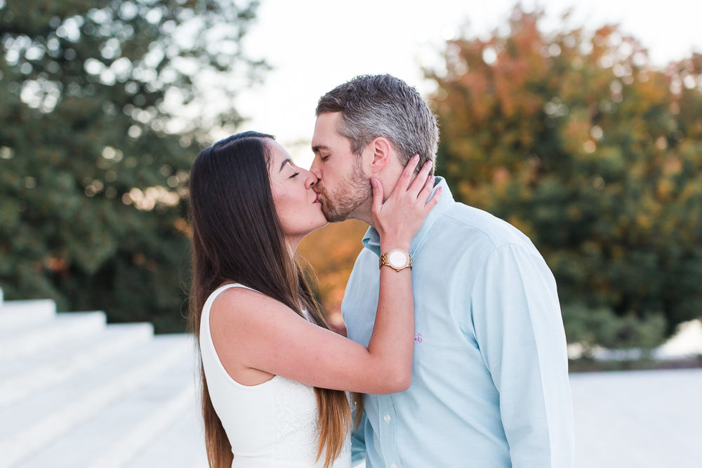 Engaged couple kisses in front of the Jefferson Memorial during their fall engagement session