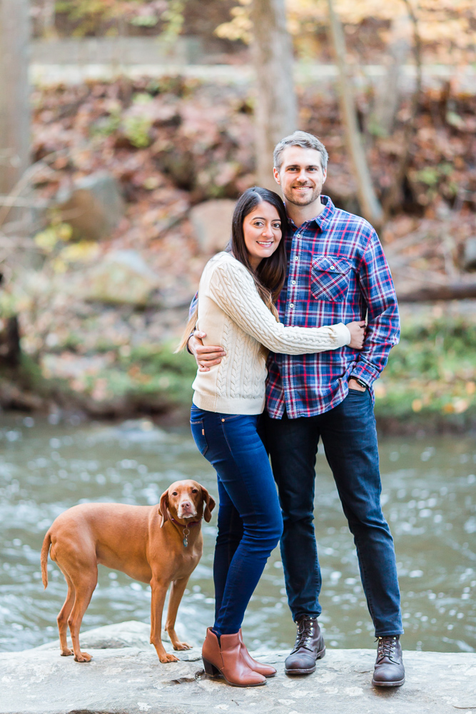 Happy couple with their dog at Rock Creek Park during a fall photo shoot