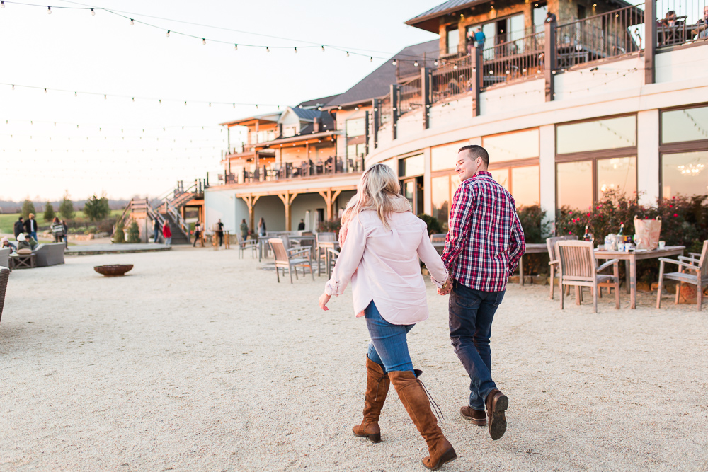 Walking hand in hand after engagement at Stone Tower Winery | Best Virginia wineries