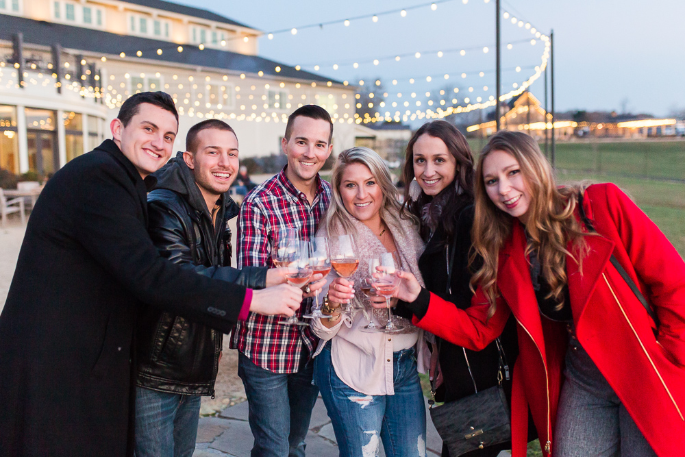 Friends toasting to celebrate after the surprise proposal on the patio under the string lights | Leesburg proposal photographer