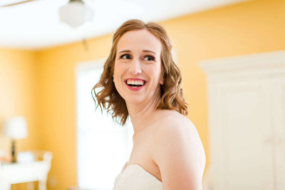 Bride laughing while putting on her wedding dress