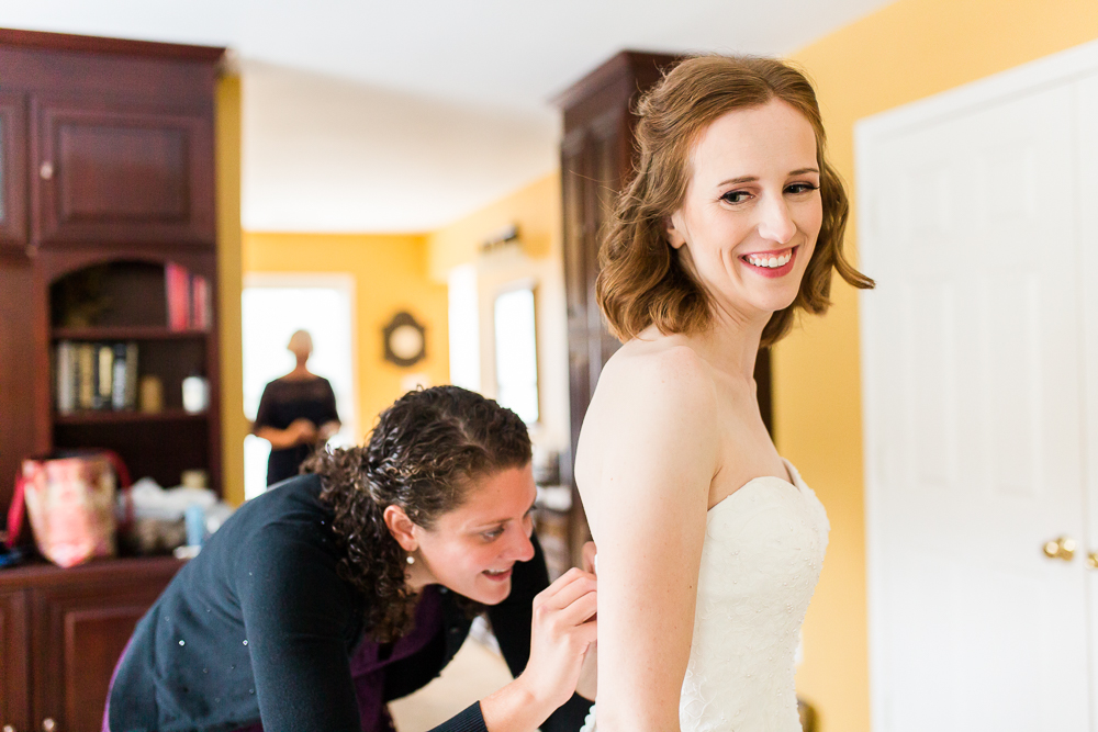 Bride smiling as she puts on her wedding dress in the bridal suite at Harvest House at Lost Creek Winery in Leesburg, VA