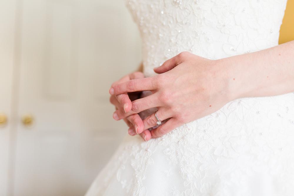 Brides hands folded on her wedding dress