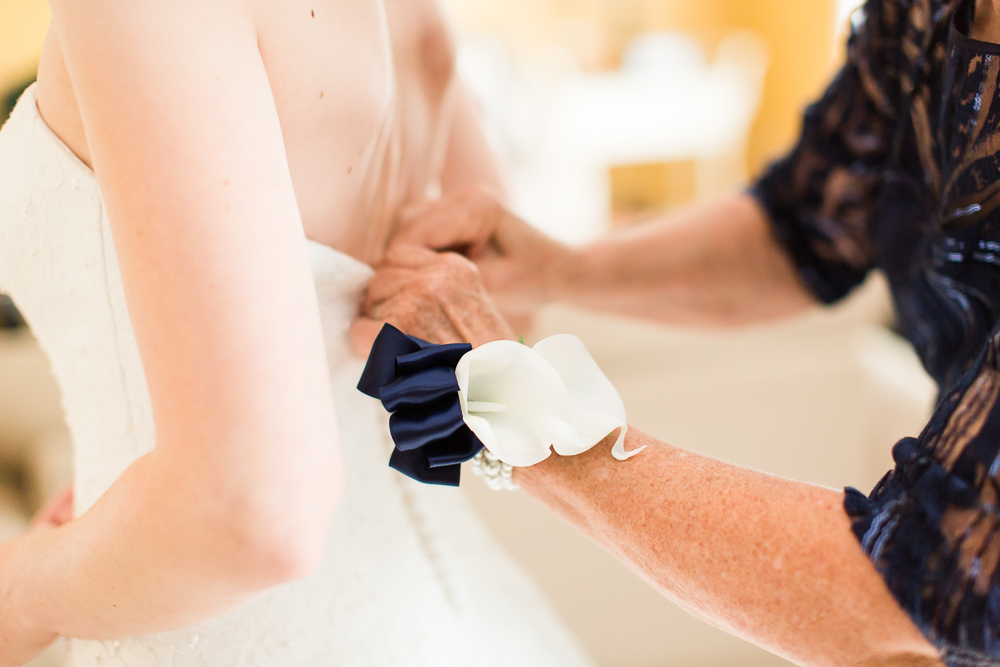 Close up photo of bride's mother buttoning up her dress