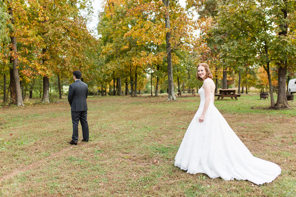 Bride walking up to the groom in the clearing behind the Harvest House at Lost Creek Winery