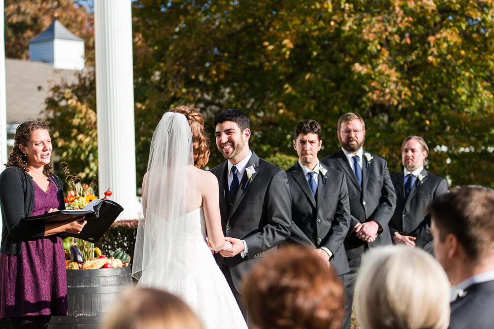 Candid photo of groom laughing during the outdoor wedding ceremony in Loudoun County, Virginia | Loudoun County Wedding Photography