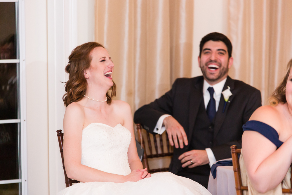 Bride and groom laughing at the toasts