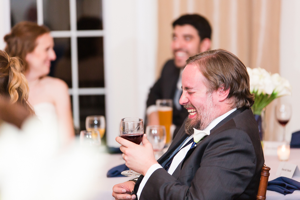 Candid photo of groomsman laughing during the wedding reception at Harvest House at Lost Creek Winery | Candid Leesburg Wedding Photographer