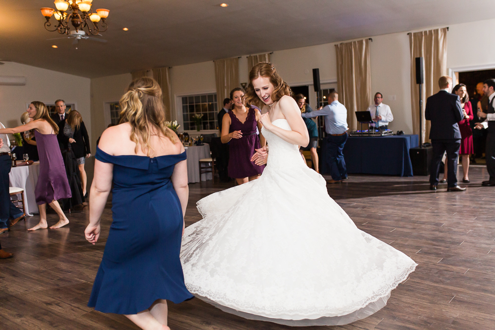 Bride dancing and twirling her dress on the dance floor during wedding reception