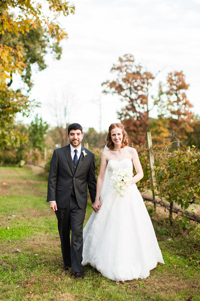 Wedding couple walking through the vineyard on their fall wedding day at Harvest House at Lost Creek Winery